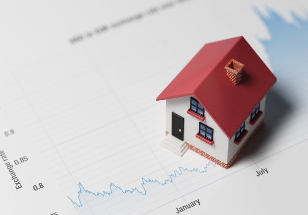 High quality 3d render of a miniature house on a blue financial chart.