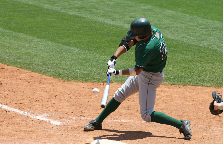 Baseball batter in green uniform hitting ball