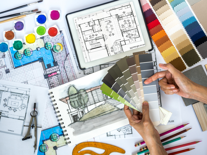 Architect, interior designer working at worktable with color swatch, sketch